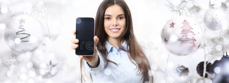 Mujer del tema de la Navidad con la sonrisa elegante del teléfono aislada en Chris foto de archivo