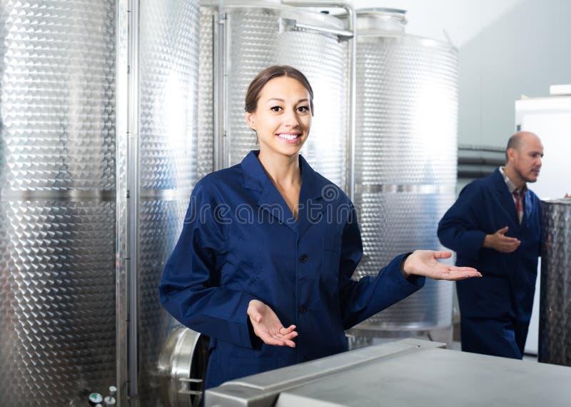 Mujer del trabajador que se coloca dentro en la pequeña fabricación del vino imágenes de archivo libres de regalías