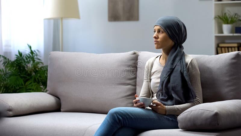 Mujer del trastorno con el té de consumición del cáncer que se sienta en casa, pensando en la remisión imagenes de archivo