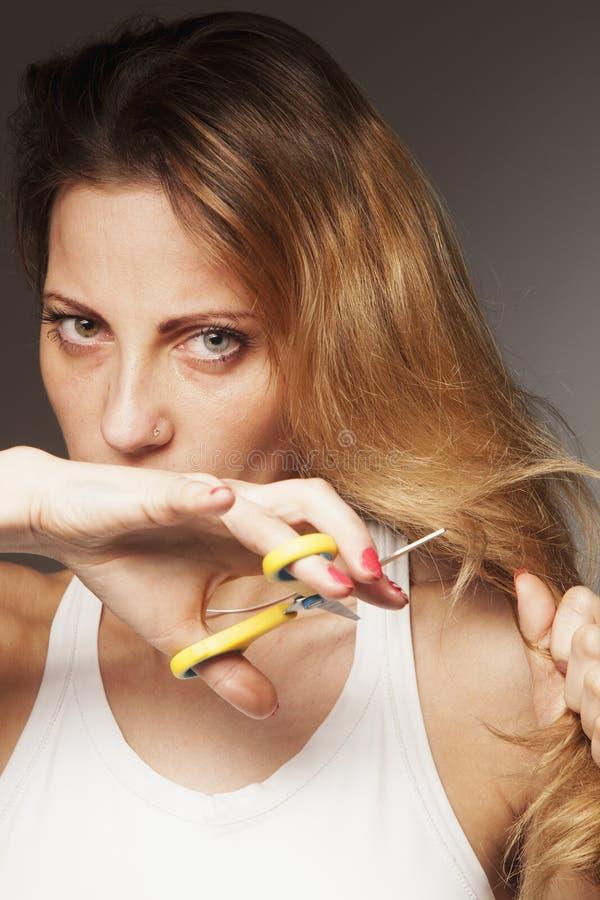 Mujer del trastorno que corta su su pelo Problema de extremos partidos fotografía de archivo libre de regalías