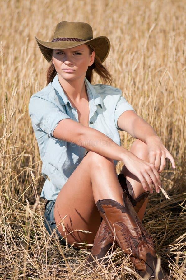 Mujer del vaquero en campo de trigo del país fotografía de archivo