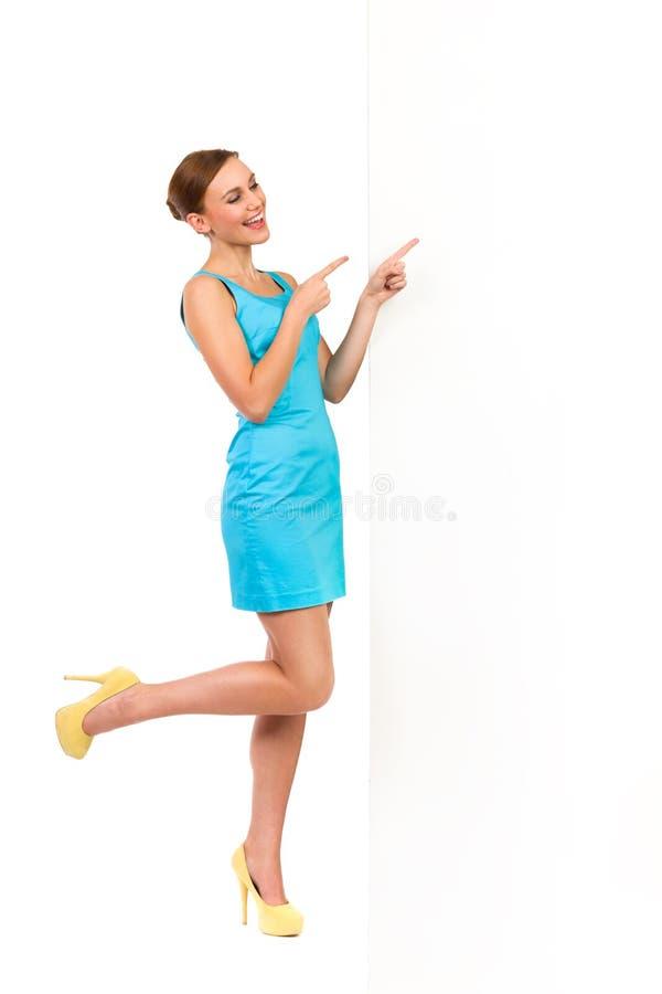 Mujer del verano que señala en el tablero blanco y la risa. imágenes de archivo libres de regalías