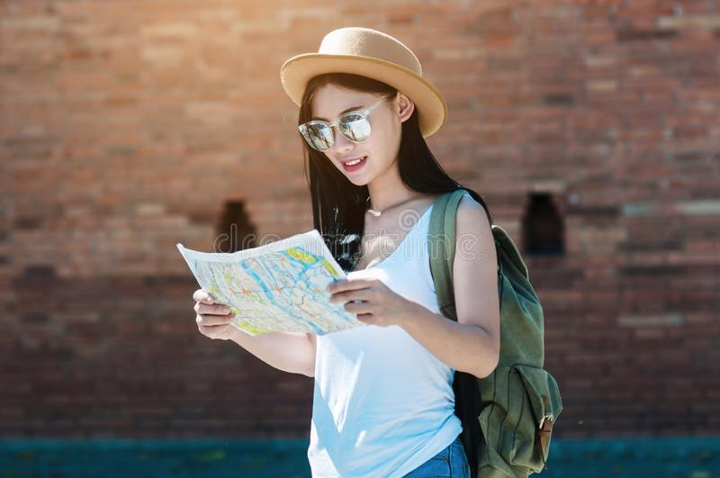 Mujer del viaje turístico que mira el mapa mientras que camina en una calle fotografía de archivo
