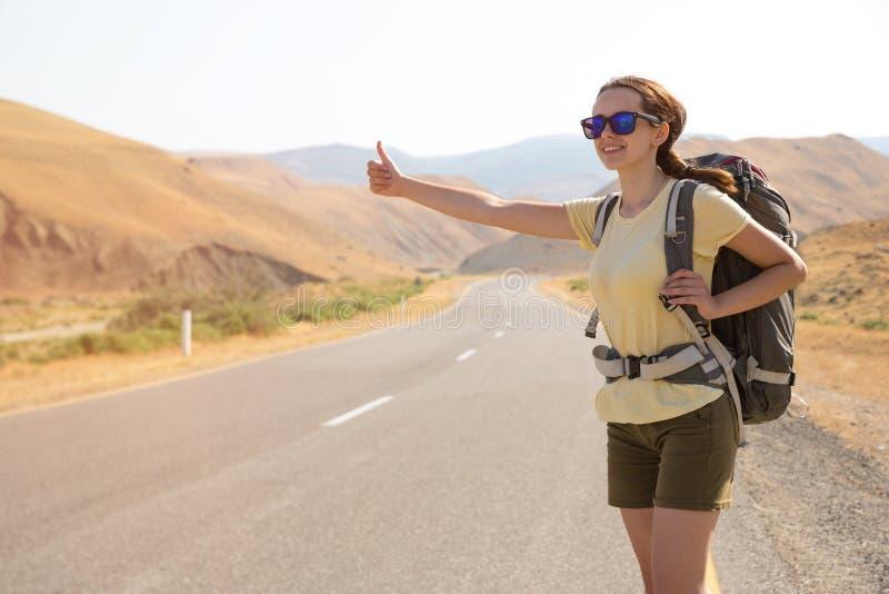 Mujer del viajero del autostopista en el camino en puesta del sol Caminante del viajero de la muchacha en el camino Vacaciones de imagen de archivo