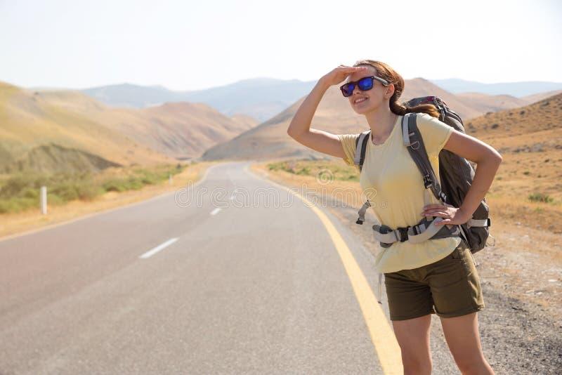 Mujer del viajero del autostopista en el camino en puesta del sol Caminante del viajero de la muchacha en el camino Vacaciones de foto de archivo