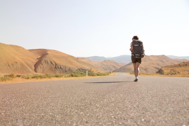 Mujer del viajero del autostopista en el camino en puesta del sol Caminante del viajero de la muchacha en el camino Vacaciones de fotografía de archivo libre de regalías