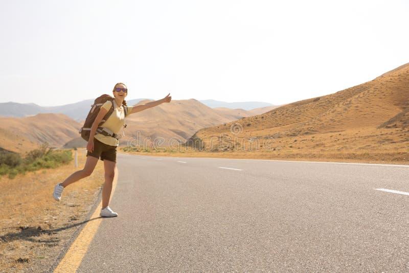 Mujer del viajero del autostopista en el camino en puesta del sol Caminante del viajero de la muchacha en el camino Vacaciones de imágenes de archivo libres de regalías
