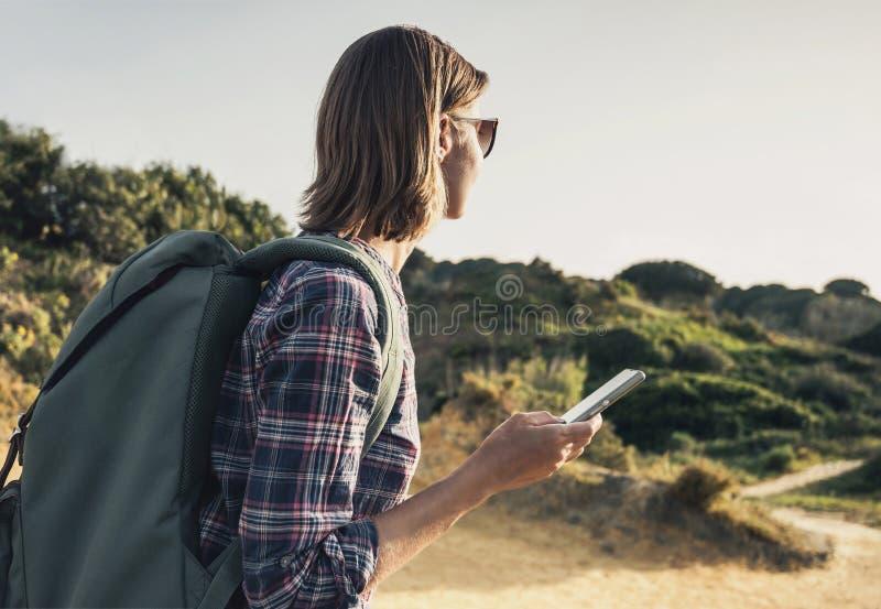 Mujer del viajero del caminante en una pista de senderismo usando smartphone, viaje y concepto activo de la forma de vida imagen de archivo