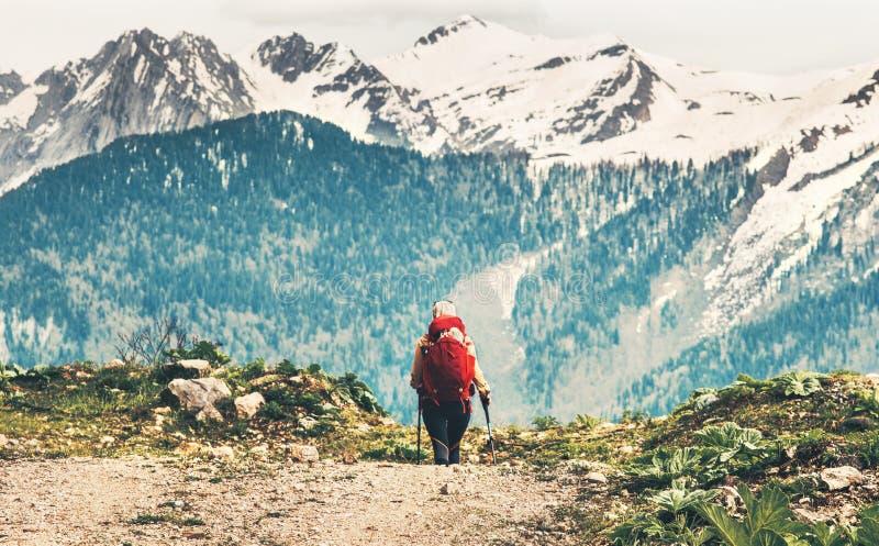 Mujer del viajero con alpinismo rojo de la mochila imagenes de archivo