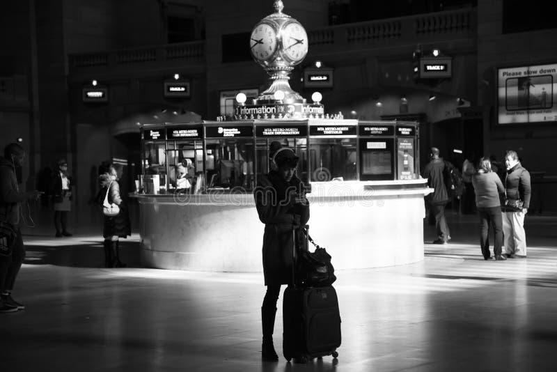 Mujer del viajero que comprueba su teléfono móvil en la estación de Grand Central foto de archivo