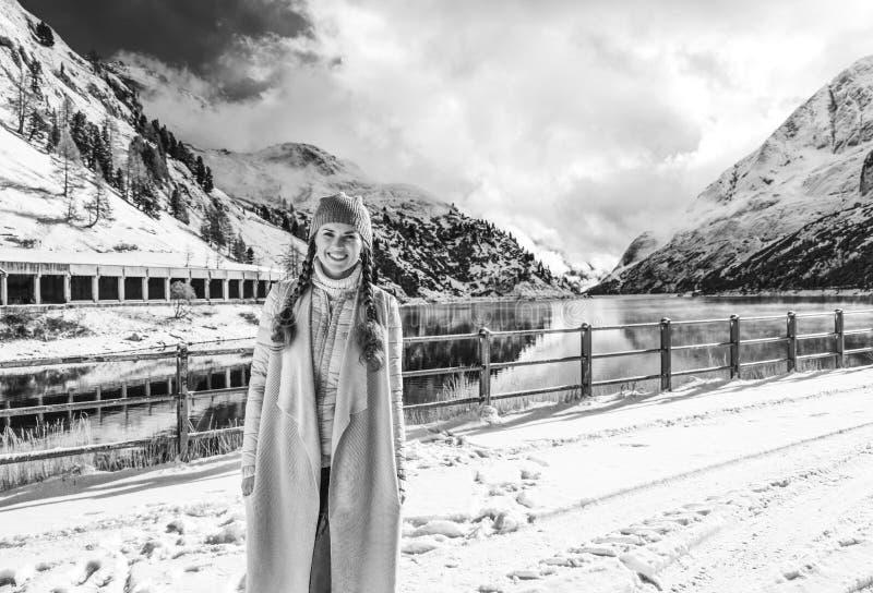 Mujer del viajero que se opone a paisaje de la montaña del invierno fotos de archivo
