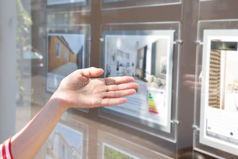 Mujer delante de la ventana del escaparate del agente inmobiliario fotografía de archivo