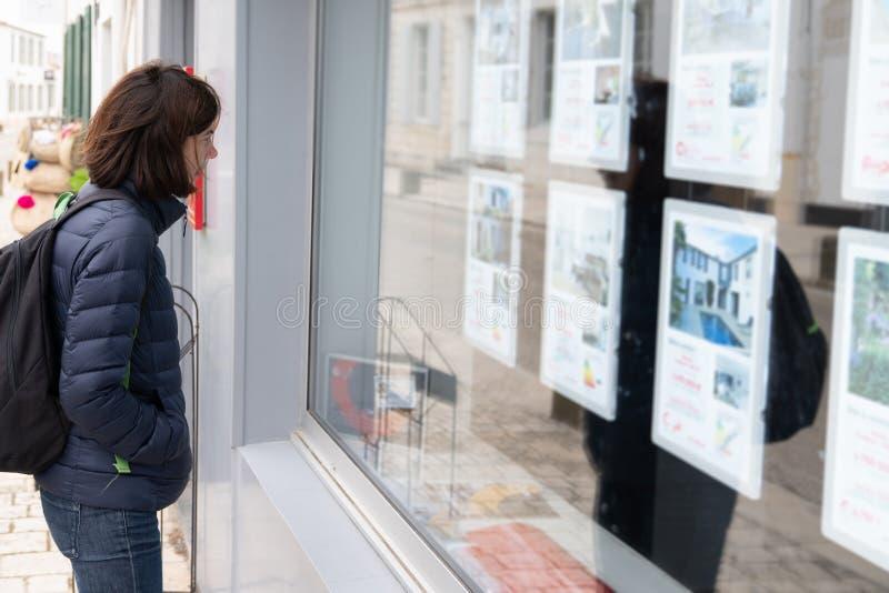Mujer delante de la ventana de una agencia inmobiliaria real foto de archivo