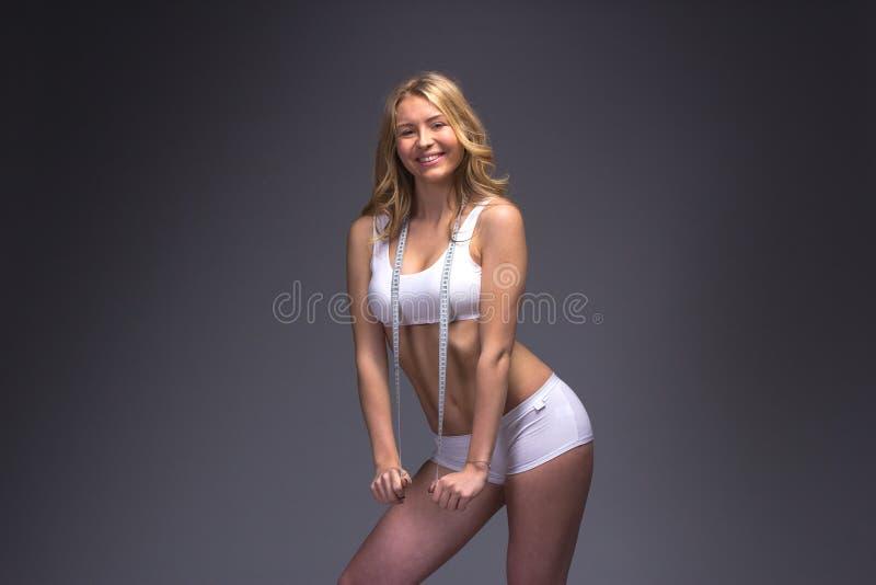 Mujer delgada atlética que mide su cintura por la cinta de la medida después de a fotos de archivo libres de regalías