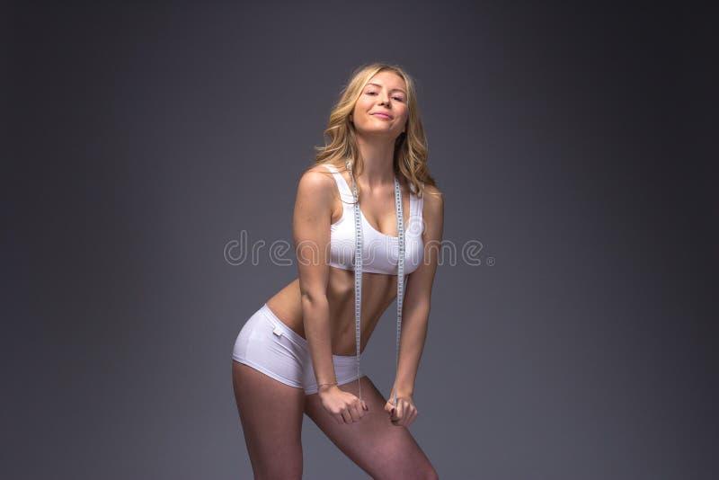 Mujer delgada atlética que mide su cintura por la cinta de la medida después de a fotos de archivo