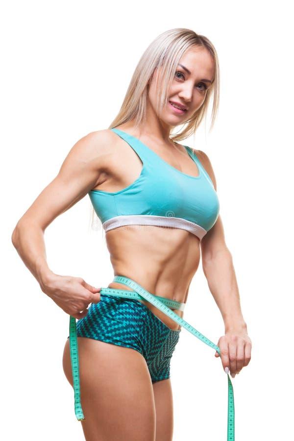 Mujer delgada atlética que mide su cintura por la cinta de la medida después de una dieta sobre fondo negro imagen de archivo libre de regalías
