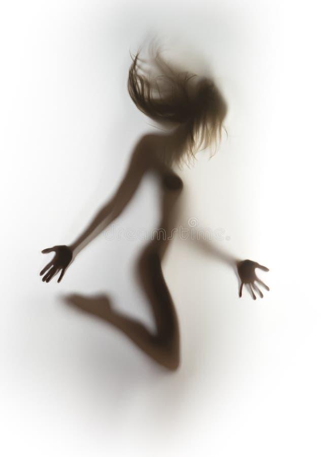 Mujer delgada, atractiva hermosa con el pelo que sopla, detrás de una cortina fotografía de archivo libre de regalías