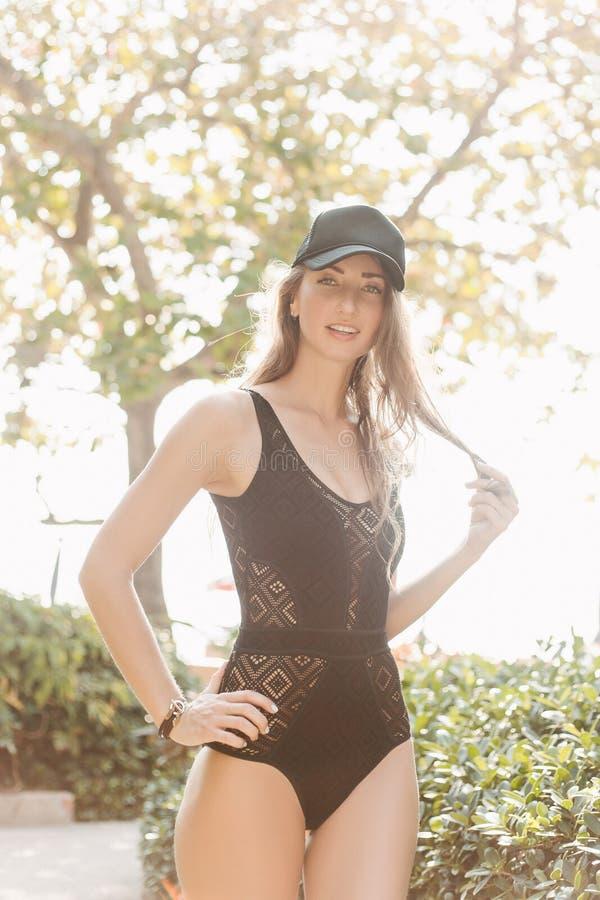 mujer delgada atractiva que presenta en traje de baño negro imagenes de archivo