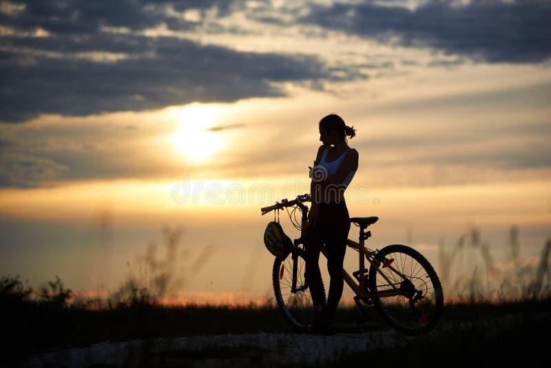 Mujer delgada, deportiva que coloca la bici cercana y la presentación imagen de archivo