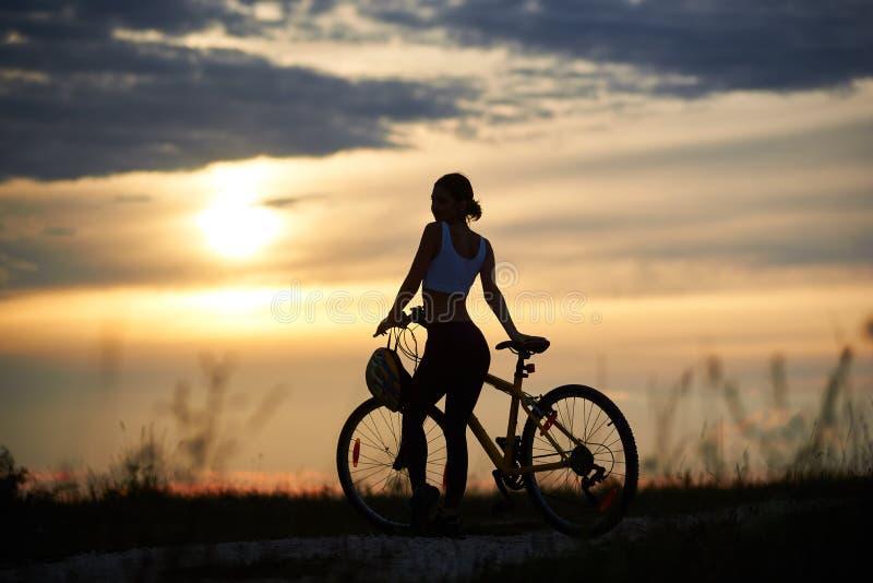 Mujer delgada, deportiva que coloca la bici cercana y la presentación foto de archivo