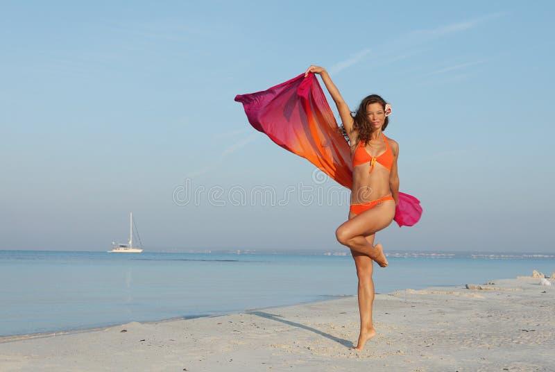 Mujer delgada en la playa que muestra su pérdida de peso fotografía de archivo