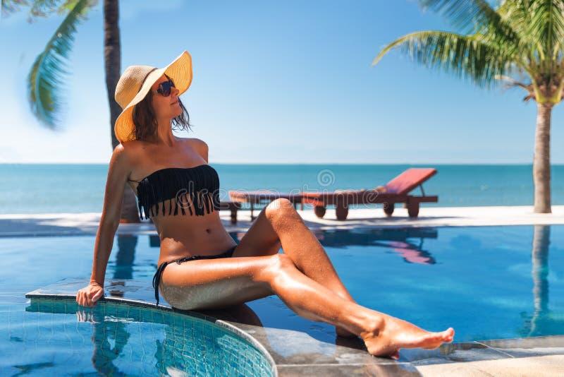 Mujer delgada en sombrero de paja de s y sunbath de las gafas de sol fotografía de archivo