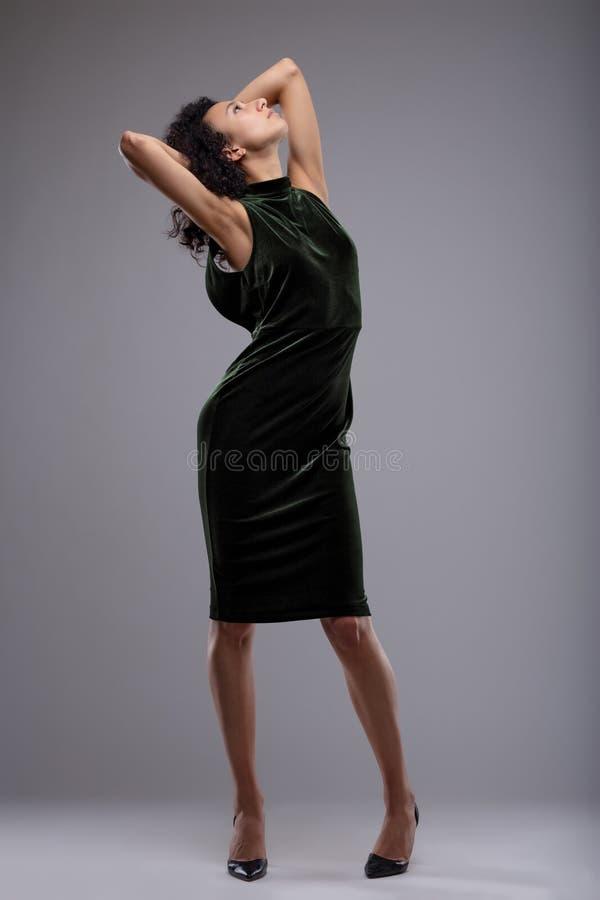 Mujer delgada en un vestido negro elegante y estiletes imagenes de archivo