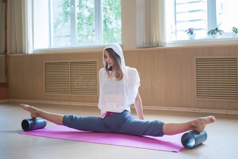Mujer delgada joven con el pelo rubio que se sienta en la estera de la yoga en fractura y que le entrena que estira - usando sopo imagen de archivo