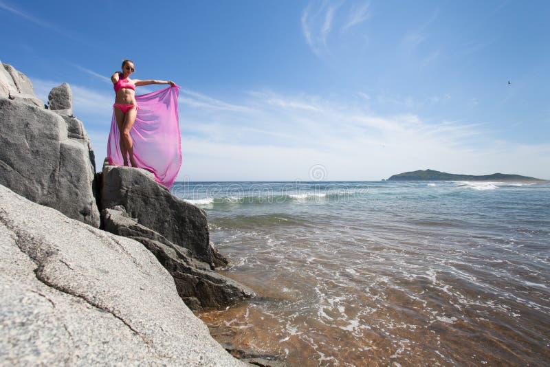 Mujer delgada joven en la orilla rocosa del mar en un traje de natación rosado y una tela rosada que agitan en el viento fotografía de archivo
