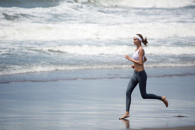 Mujer delgada joven que corre en la playa fotos de archivo