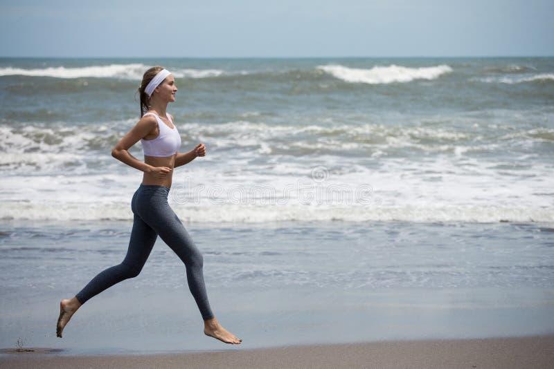 Mujer delgada joven que corre en la playa fotografía de archivo libre de regalías