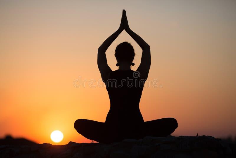 Mujer delgada que hace yoga sobre el sol anaranjado imagenes de archivo