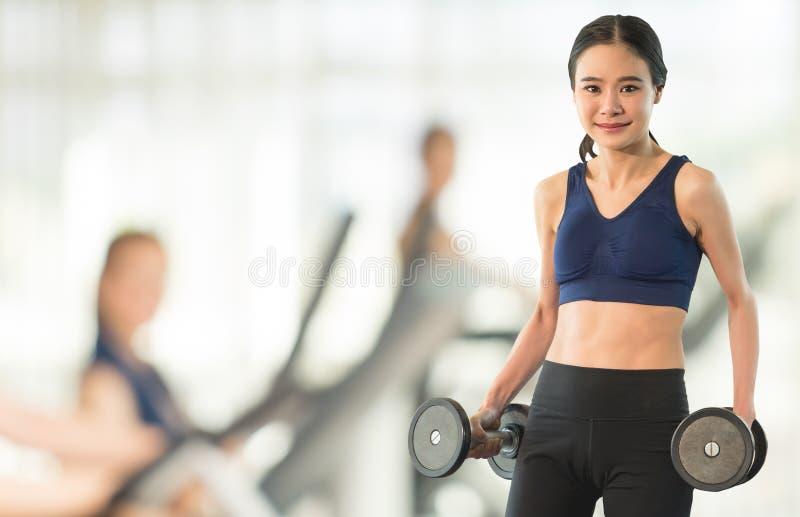 Mujer delgada que lleva a cabo pesa de gimnasia en gimnasio del extracto de la falta de definición fotografía de archivo