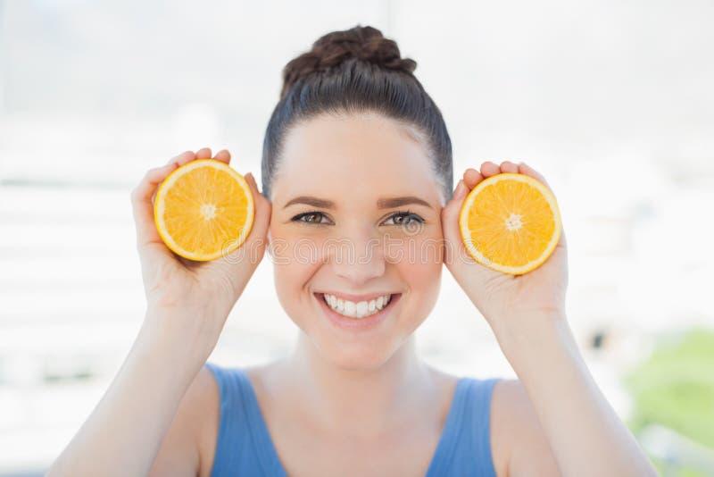 Mujer delgada sonriente en la ropa de deportes que lleva a cabo rebanadas de naranja fotografía de archivo