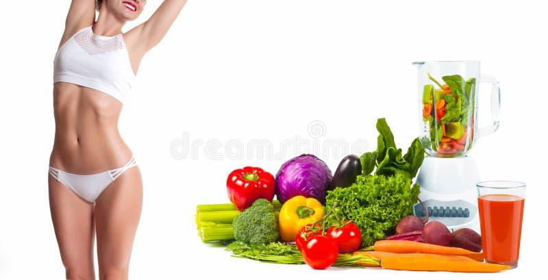 Mujer delgada y deportiva, concepto de la dieta con las verduras frescas foto de archivo