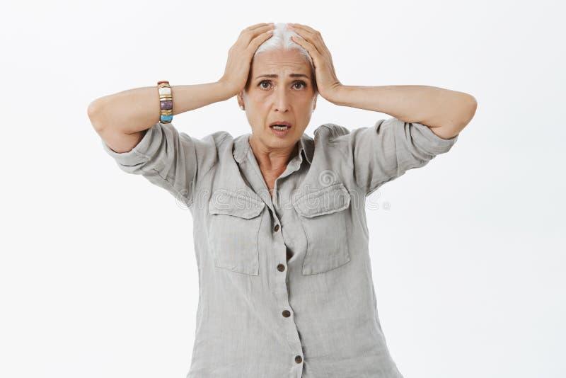 Mujer demasiado vieja para tales nervios Retrato de la señora mayor preocupada en cuestión y confusa con el pelo blanco que lleva fotos de archivo