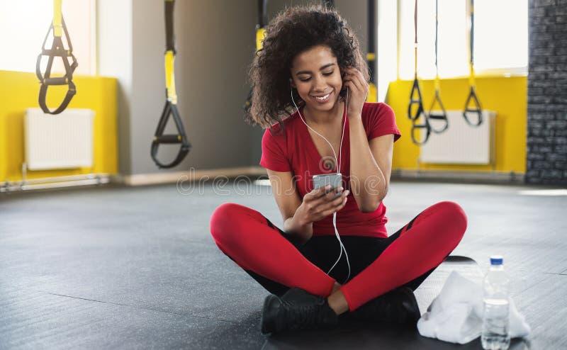 Mujer deportiva afroamericana que escucha la música en smartphone en gimnasio fotos de archivo libres de regalías