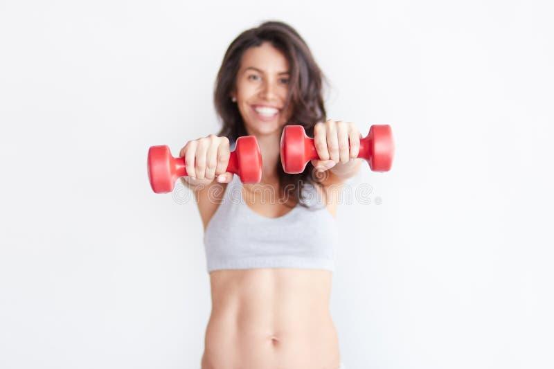 Mujer deportiva alegre sonriente que lleva a cabo pesas de gimnasia rojas imágenes de archivo libres de regalías