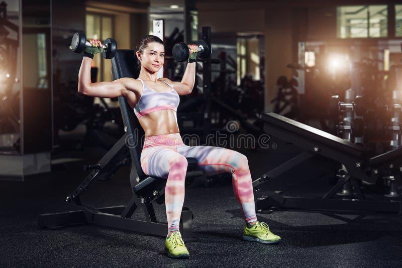 Mujer deportiva atractiva que ejercita en gimnasio con pesas de gimnasia imagen de archivo libre de regalías