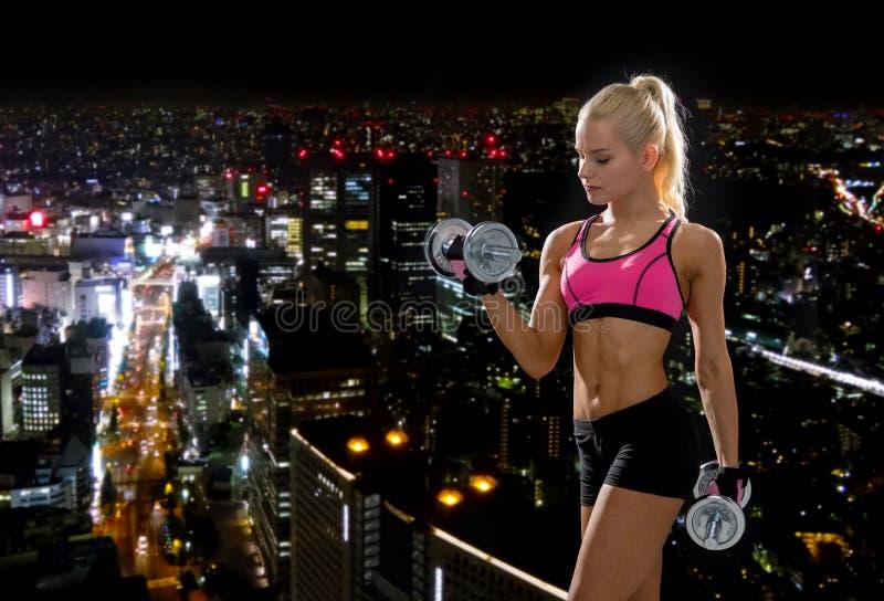 Mujer deportiva con pesas de gimnasia de acero pesadas imagen de archivo libre de regalías
