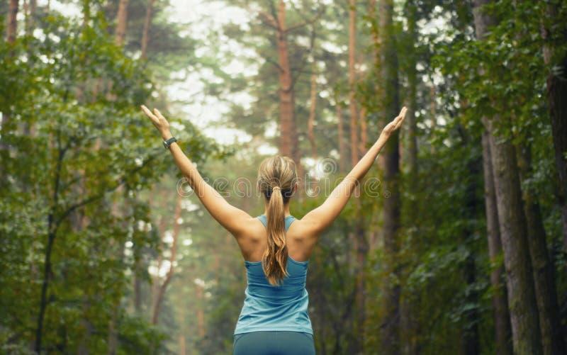Mujer deportiva de la aptitud sana de la forma de vida temprano en área del bosque imagenes de archivo