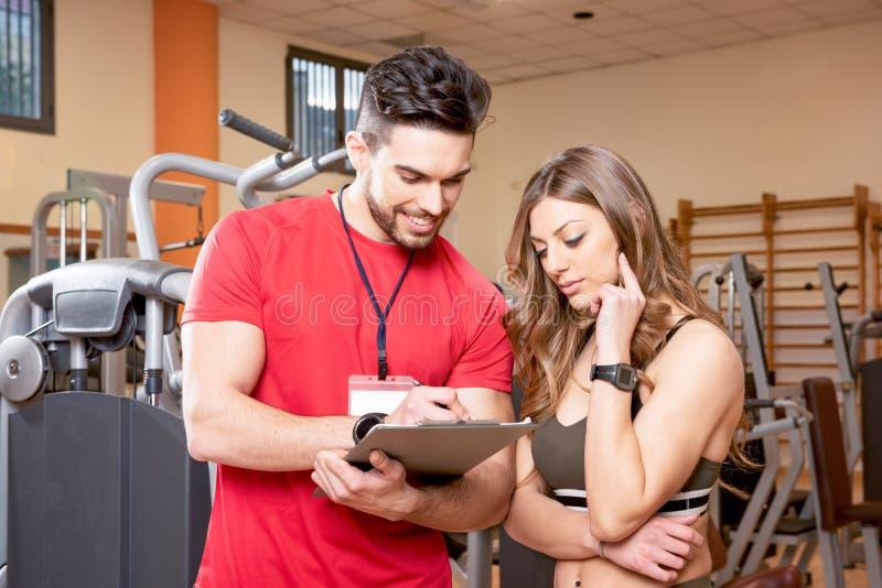Mujer deportiva del anuncio del hombre que usa la tableta de la PC en el gimnasio Pares de los instructores jovenes de la aptitud imagenes de archivo