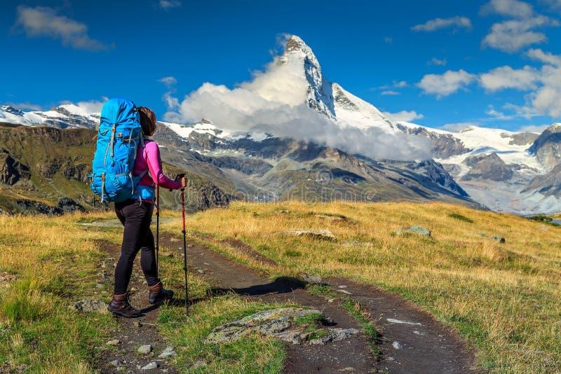 Mujer deportiva del caminante con el pico de Cervino en el fondo, Valais, Suiza fotos de archivo