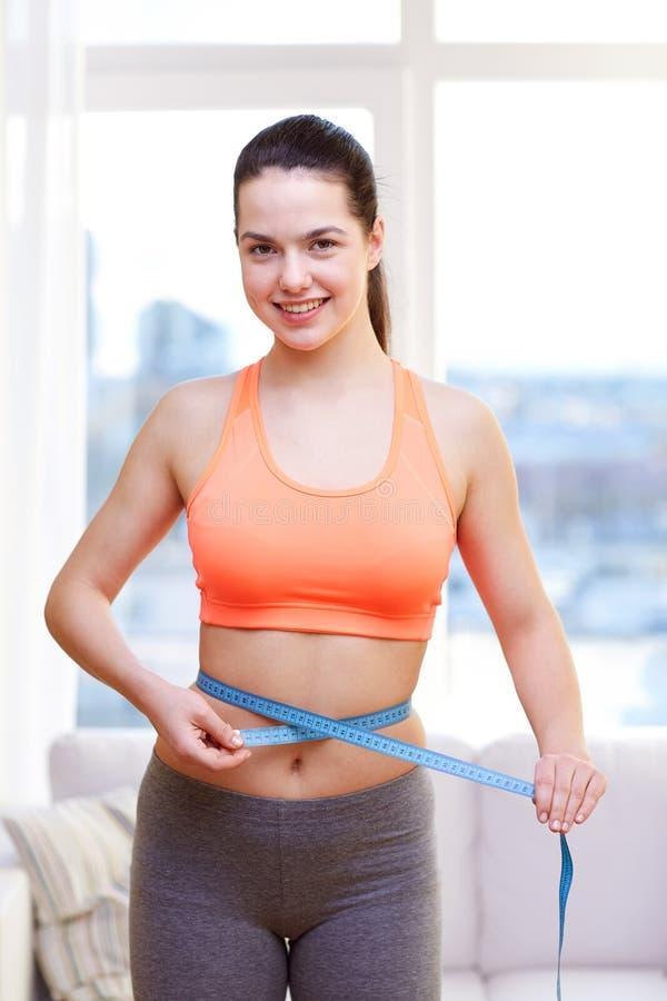 Mujer deportiva feliz que mide su cintura con la cinta fotografía de archivo libre de regalías