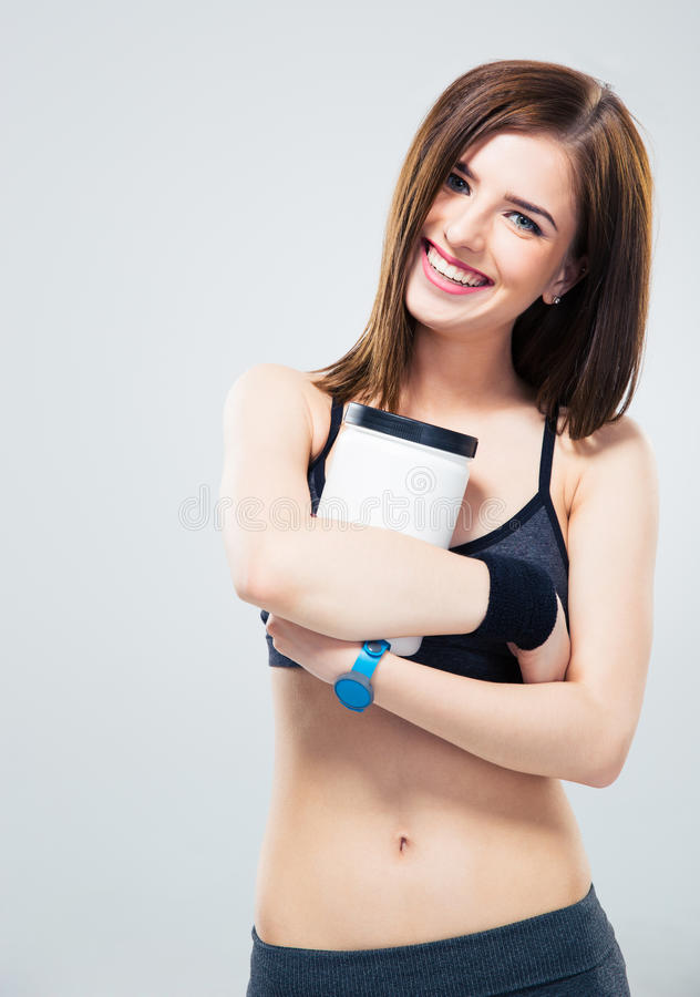 Mujer deportiva feliz que sostiene el tarro de proteína fotos de archivo libres de regalías