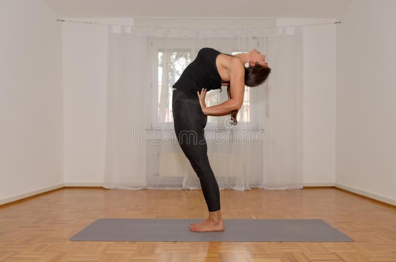 Mujer deportiva flexible que se resuelve en casa fotos de archivo