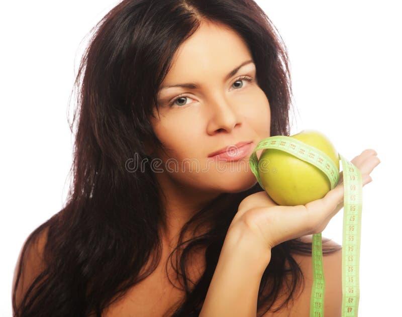Mujer deportiva hermosa con la manzana y la cinta métrica verdes foto de archivo libre de regalías