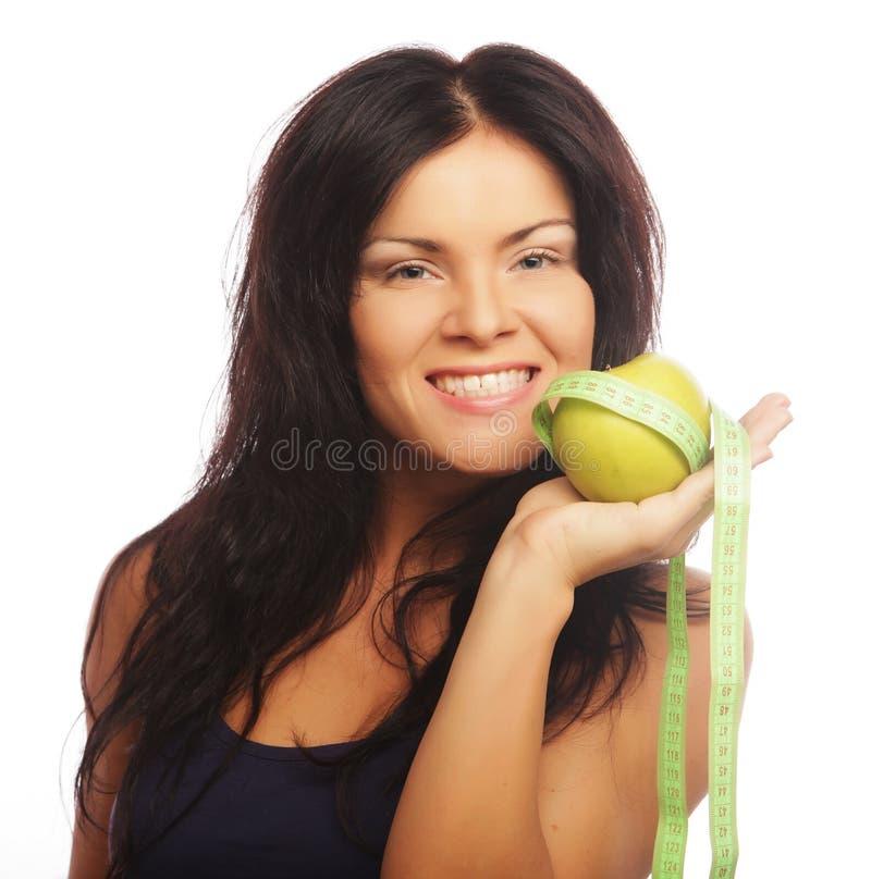 Mujer deportiva hermosa con la manzana y la cinta métrica verdes fotografía de archivo libre de regalías