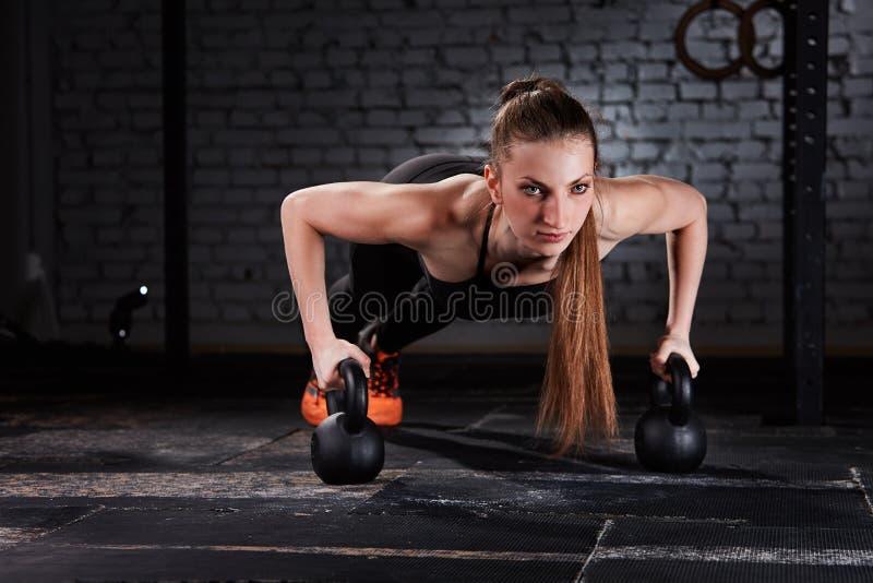 Mujer deportiva hermosa joven en hacer negro del sportwear flexiones de brazos con el kettlebell en el gimnasio del crossfit imagen de archivo libre de regalías