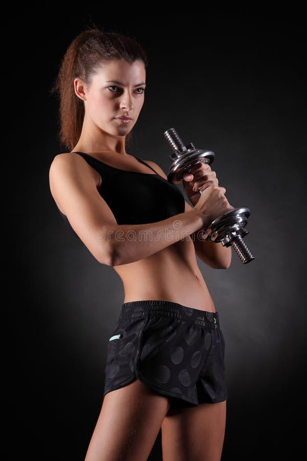 Mujer deportiva hermosa que se resuelve con pesas de gimnasia fotos de archivo libres de regalías